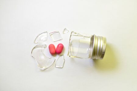 A broken small glass bottle with a metal cap, two pink heart-shaped tablets fell out of it, on a white background, flat, top view