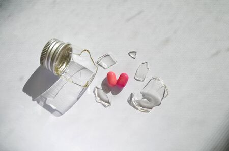A broken small glass bottle with a metal cap, two pink heart-shaped tablets fell out of it, on a dirty white background, side view Banco de Imagens - 131637965