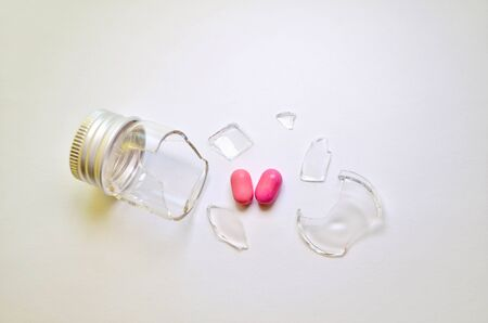 A broken small glass bottle with a metal cap, two pink heart-shaped tablets fell out of it, on a white background, side view Banco de Imagens - 131637967