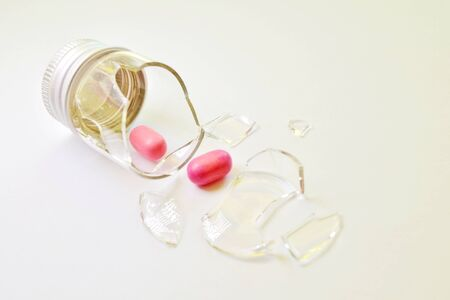 A broken small glass bottle with a metal cap, two pink tablets fell out of it, on a white background, flat Banco de Imagens - 131637992