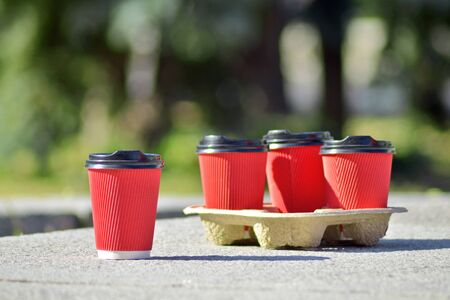 Four red paper coffee cups with black lids on a stand stand on a concrete surface on a blurred background of green trees and city