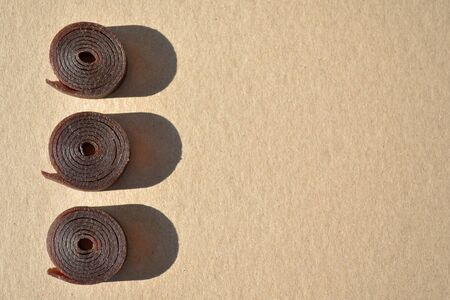 Three pieces of round pastille rolled up on a roll, they are lying vertically on cardboard brown paper with shadows from the sun, with copyspace