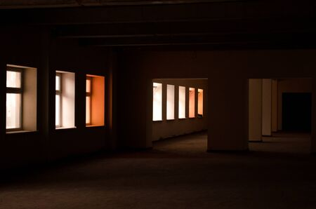 Empty dark space of a monolithic building with supports and windows with colored light from the windows, without repair Stock Photo