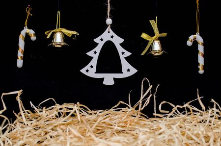 Background for a photo collage on a Christmas theme with hay, a white Christmas tree, bells and sweets on a black color