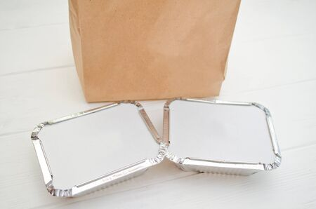 Mockup for delivery of fast food, foil plates with a cardboard cover, near a paper bag on a white background Banco de Imagens