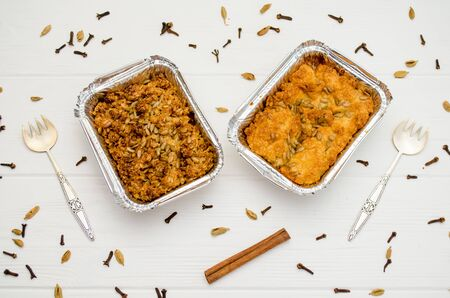 Indian food, fruit pies, subhadra and mithai, in foil plates on a white background, sprinkled with seeds, spices, cinnamon stick, with two forks Banco de Imagens