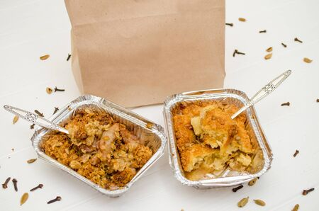 Indian food, fruit pies, subhadra and mithai, in foil plates on a white background, sprinkled with seeds, spices, two forks inside plates near paper bag, mockup Banco de Imagens