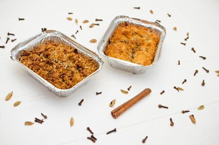 Indian food, fruit pies, subhadra and mithai, in foil plates on a white background, sprinkled with seeds, spices, cinnamon stick, side view