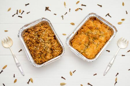 Indian food, fruit pies, subhadra and mithai, in foil plates on a white background, sprinkled with seeds, spices with two forks