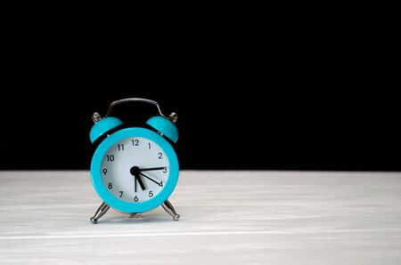 Blue retro alarm clock on a black and white wooden background, with a copyspace, a concept of the morning, a countdown