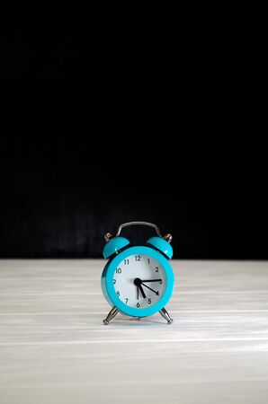 Blue retro alarm clock on a black and white wooden background, with a copyspace, a concept of morning, a countdown Banco de Imagens