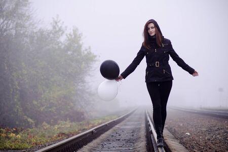 Ragazza solitaria in abiti neri che cammina sui binari in una nebbia. Tiene in mano un palloncino bianco e nero che vola via. Concetto di scelta, obiettivo, bene e male, modo di vivere