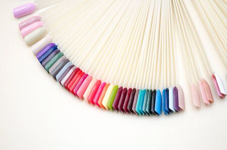 Palette of nail designs of different colors with gel polish on a white tips and background. Collection of plastic testers for nail polish with copyspace