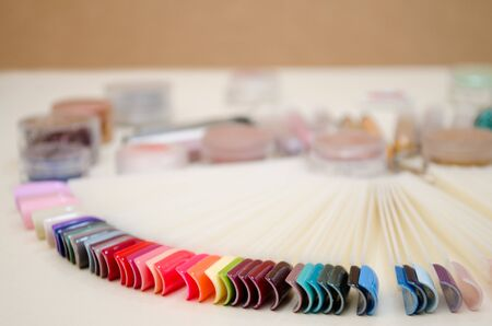 Palette of nail designs of different colors with gel polish on a white tips and background, jars with sparkles and decor for nail design with copyspace Reklamní fotografie