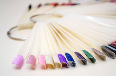 Palette of nail designs of different colors with gel polish on a white tips and background. Collection of plastic testers for nail polish