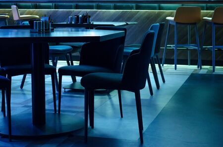Tables and upholstered chairs in a cafe in subdued dark intimate blue light Foto de archivo
