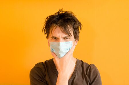 Man with mask to protect him from virus. Concept of the epidemic of the coronavirus. Tired man with uncombed hair on yellow background