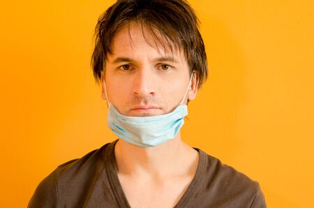 Man with blue mask on his chin to not protect him from virus, on yellow background, epidemic coronavirus put on mask wrong concept. Tired man with uncombed hair on yellow background Stock Photo