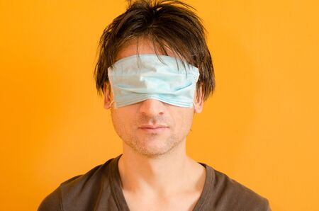 Man with blue mask on his eyes to not protect him from virus, on yellow background, epidemic coronavirus medical put on mask wrong concept. Tired man with uncombed hair on yellow background