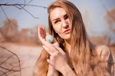 Young caucasian blonde girl in a light boho style dress, sitting on a tree with a blue egg similar to dragon egg from fantasy, like a mother of dragons, photo for cover of a book, movie or music album