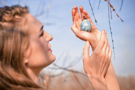 Young blonde girl in a light dress, holds a blue egg in her hands, like dragon egg from fantasy, against blue sky and branches, like a mother of dragons, photo for cover of book, movie or music album Standard-Bild