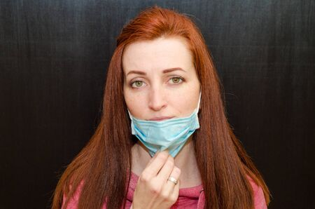 Young caucasian redhaired girl with green eyes, in a medical mask in a pink sweater on a black background, coronavirus epidemic, quarantine Foto de archivo