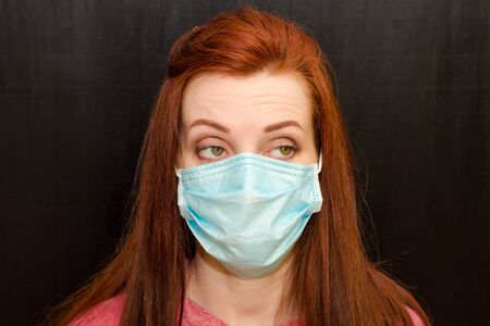 Young caucasian redhaired girl with green eyes, in a medical mask in a pink sweater on a black background, coronavirus epidemic, quarantine