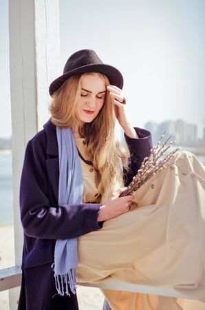 Young caucasian blonde girl in a boho dress, coat and hat in spring on city beach, in lifeguard house under rays of spring sun with willow branches, smiling