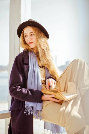 Young caucasian blonde girl in boho dress, coat and hat in spring on city beach, in lifeguard house under rays of spring sun, reading a book, smiling Standard-Bild