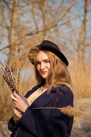 Young caucasian blonde girl in a boho dress, coat and hat in spring on beach, under rays of spring sun with willow branches, smiling dream about something Standard-Bild