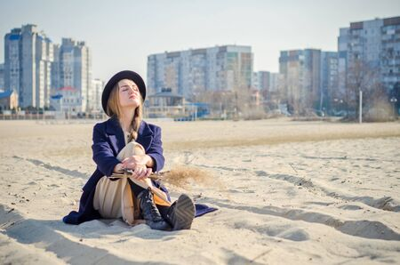 Young caucasian blonde girl in light dress, coat and hat on beach, under rays of spring sun with reeds branches, sitting on sand against background of urban high-rise buildings, dream about something