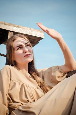 Beautiful young caucasian blonde girl, in a light boho dress, sits on an old wooden construction, a bridge over the water against blue sky in countryside