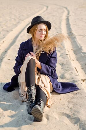 Young caucasian blonde girl in a light dress, coat and hat on beach, under rays of spring sun with reeds branches, with closed eyes, dream about something