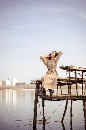 Beautiful young caucasian blonde girl, in a light boho dress, sits on an old wooden construction, a bridge over the water against blue sky in countryside on background of city