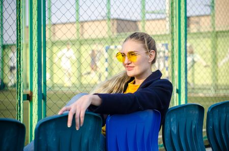 Beautiful young blonde girl in a yellow sweater and blue jeans, white sneakers and a blue coat sits on the seats for spectators on the sports field in yellow glasses