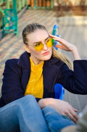 Beautiful young blonde girl in a yellow sweater and blue jeans, white sneakers and a blue coat sits on the seats for spectators on the sports field in yellow glasses Standard-Bild