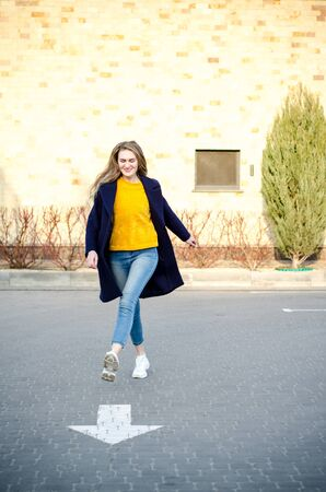 Beautiful young blonde girl in a yellow sweater and blue jeans, white sneakers and a blue coat, having fun, laughing in an empty parking lot, near a white direction arrow on asphalt