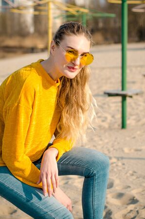 Beautiful young blonde girl in a yellow sweater and blue jeans, sits on beach against a blue sky in yellow glasses