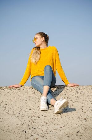 Beautiful young blonde girl in a yellow sweater and blue jeans, white sneakers sits on a concrete surface against a blue sky in yellow glasses Standard-Bild