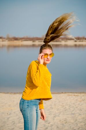 Beautiful young blonde girl in a yellow sweater and blue jeans, stay on beach against a blue sky and water in yellow glasses and touch her hair