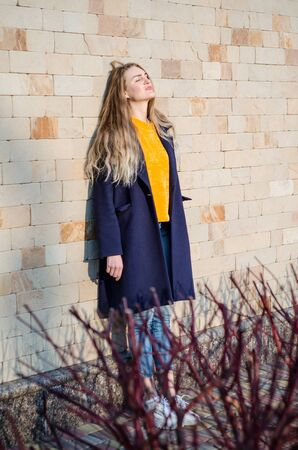 Beautiful young blonde girl in a yellow sweater and blue jeans, white sneakers and a blue coat, in yellow glasses stay against a brick wall