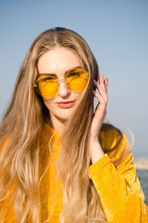 Beautiful young blonde girl in a yellow sweater and blue jeans, sits on a concrete surface against a blue sky in yellow glasses
