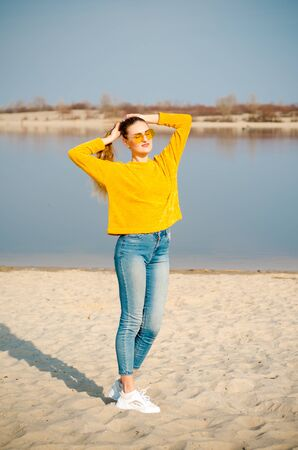 Beautiful young blonde girl in a yellow sweater and blue jeans, white sneakers stay on beach against a blue sky and water in yellow glasses and touch her hair