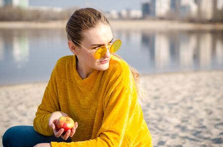 Beautiful young blonde girl in a yellow sweater and blue jeans, stay on beach against a blue sky and water in yellow glasses and hold red apple Standard-Bild
