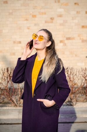 Beautiful young blonde girl in a yellow sweater and blue jeans, white sneakers and a blue coat, in yellow glasses speaks on the phone against a brick wall