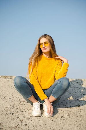 Beautiful young blonde girl in a yellow sweater and blue jeans, white sneakers sits on a concrete surface against a blue sky in yellow glasses Stok Fotoğraf