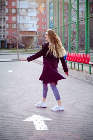 Beautiful young blonde girl in blue jeans, white sneakers and a blue coat, having fun, laughing in an empty parking lot, near a white direction arrow on asphalt