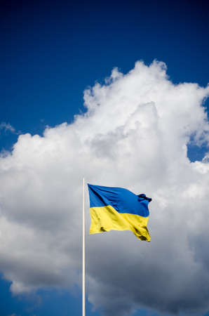 Blue and yellow Ukrainian national flag on a flagpole against a blue sky and white clouds, flag waving in the wind