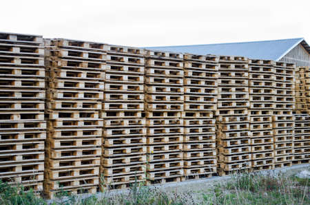 Stacks of wooden pallets for the industrial transportation by trucks or for processing into furniture