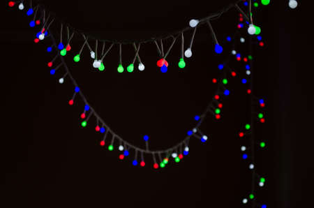Christmas background with a glowing colorful garland lights on black background. New Year postcard Stok Fotoğraf